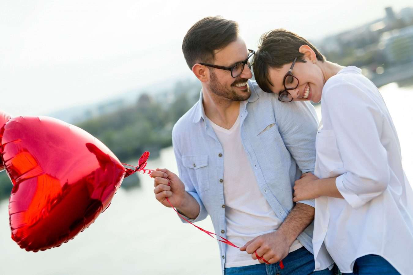 Young couple in love dating and smiling outdoor while holding heart baloons