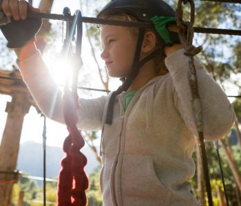 little-girl-wearing-helmet-standing-near-zip-line-in-the-forest